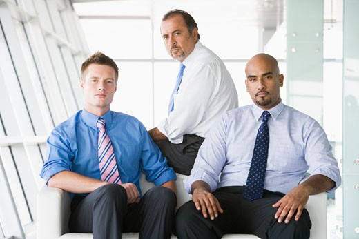 Three businessmen sitting indoors (high key/selective focus) : Stock Photo
