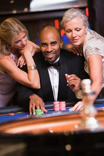 Three people in casino playing roulette smiling (selective focus) : Stock Photo