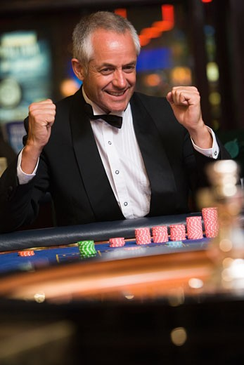 Stock Photo: 1799R-21043 Man in casino winning roulette smiling (selective focus)