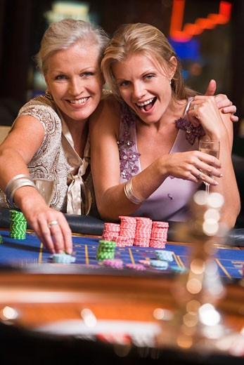 Stock Photo: 1799R-21054 Two women in casino playing roulette and smiling (selective focus)