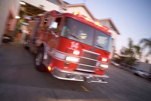 Fire engine leaving firehouse (blur) : Stock Photo