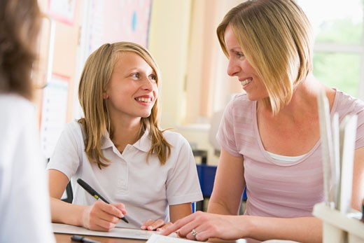Stock Photo: 1799R-21638 Student in class taking notes with teacher helping