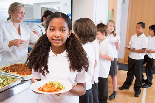 Students in cafeteria line with one holding her healthy meal and looking at camera (depth of field) : Stock Photo