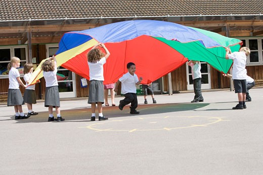 Stock Photo: 1799R-21825 Students outdoors during recess playing with a parachute