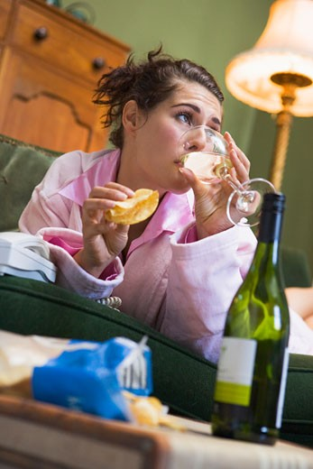 Young woman at home drinking wine and eating potato chips : Stock Photo