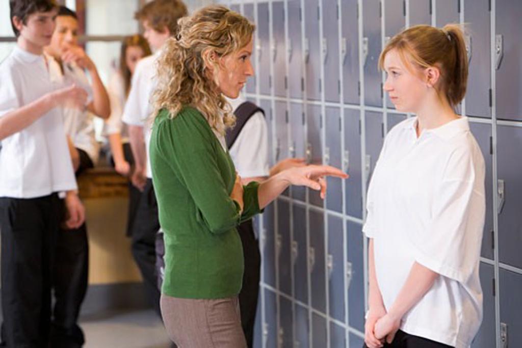 Female teacher reprimanding a female student : Stock Photo