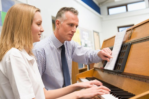Stock Photo: 1799R-22161 Female student learning piano with teacher in classroom
