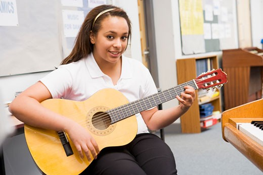 Stock Photo: 1799R-22167 Female student learning guitar in classroom