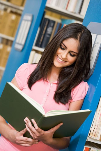 Stock Photo: 1799R-22389 Woman in library reading book (depth of field)
