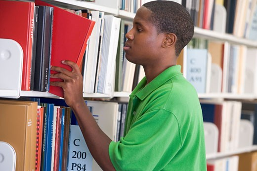 Stock Photo: 1799R-22404 Man in library pulling book off a shelf (depth of field)
