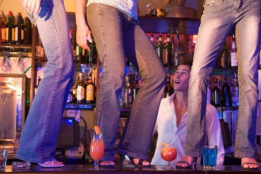 Young people dancing on a bar counter with bartender looking on : Stock Photo