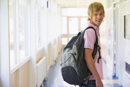 Student standing in corridor (selective focus) : Stock Photo
