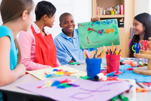 Stock Photo: 1799R-22997 Student showing teacher and classmates his artwork (selective focus)