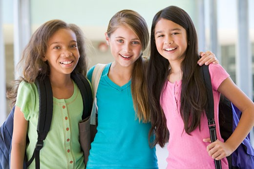 Stock Photo: 1799R-23031 Three students standing outside school together smiling (selective focus)