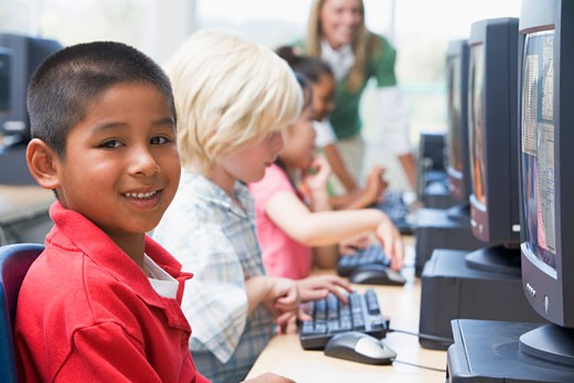 Four children at computer terminals with teacher in background (depth of field/high key) : Stock Photo