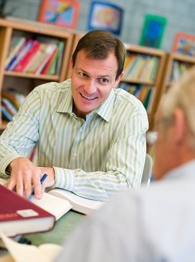 Two men in library with notepads talking (selective focus) : Stock Photo