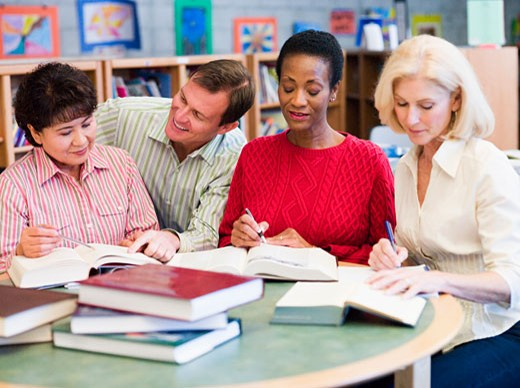 Stock Photo: 1799R-23213 Three women sitting in library with books and notepads while a man leans over them (selective focus)