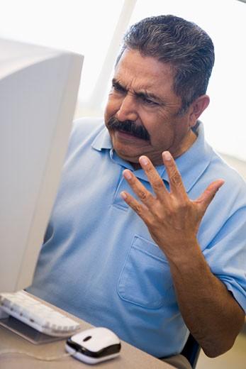 Man at computer looking at monitor frustrated (high key) : Stock Photo