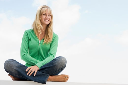 Blonde woman in a green sweater sitting outdoors : Stock Photo