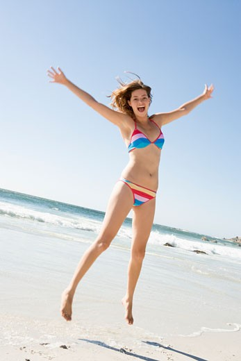 Woman in a two piece bathing suit jumping on a beach : Stock Photo