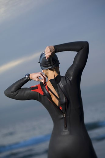 Stock Photo: 1799R-24865 Rear view of a mid adult woman zipping up her wetsuit