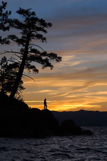 Stock Photo: 1799R-25359 Silhouette of a woman standing at the lakeside, Lake Tahoe, California, USA