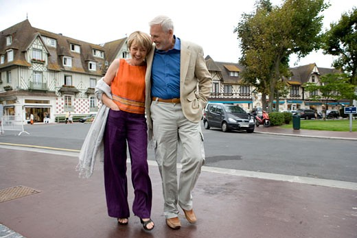 Mature couple walking on a road : Stock Photo
