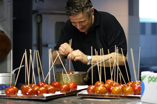 Stock Photo: 1799R-26629 Mature man dipping a candied apple