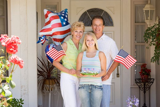 Family at front door on fourth of July with flags and cookies smiling : Stock Photo