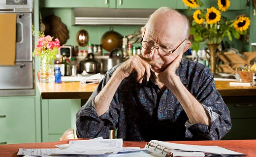 Senior man working on bills : Stock Photo