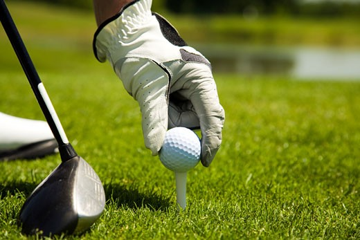 Male golfer positioning a golf ball on a tee : Stock Photo