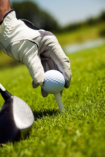 Stock Photo: 1799R-28505 Male golfer positioning a golf ball on a tee