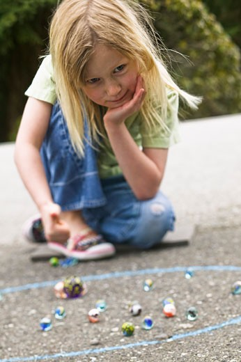 Girl playing with marbles : Stock Photo
