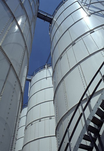 Low angle view of oil storage tanks : Stock Photo