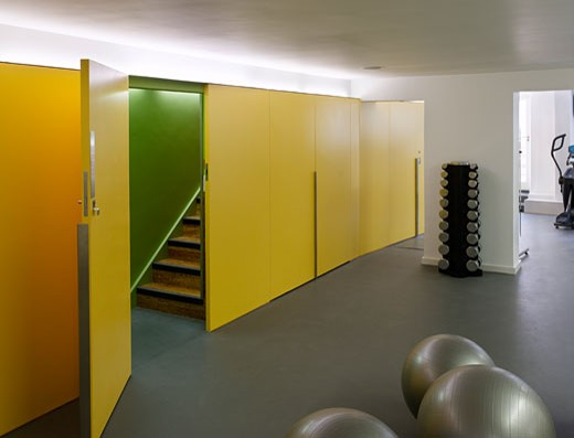 Fitness cafe gym with yellow storage wall., Fitness Cafe, 97 Boundary Road, London, NW8 St John's Wood, United Kingdom, DMD Architects : Stock Photo