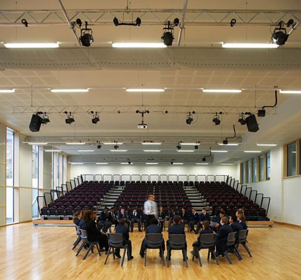 Stock Photo: 1801-38049 St Mary Magdalene Academy, London, United Kingdom, Feilden Clegg Bradley Architects, St mary magdalene academy hall with tiered seating and circle of pupils.