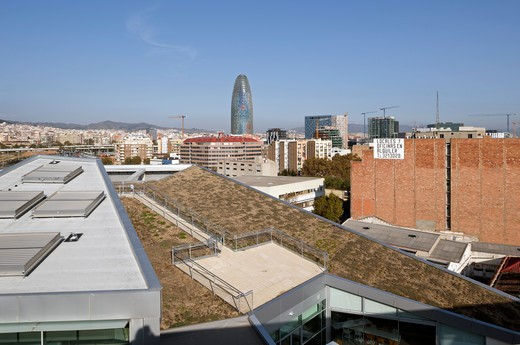 Stock Photo: 1801-71592 William Macdonough , Partners Ecourban Building Barcelona Poble Nou 22@ District L Exterior View Of Triangular Building Showing Chimney Doors  Roof Garden With City In The Background