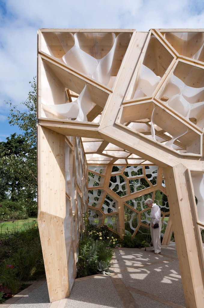 Stock Photo: 1801-72470 Times Eureka Pavilion, Kew, United Kingdom. Architect NEX, 2011. Exterior of entrance looking inside towards walls and flower bed with woman looking at flower bed.