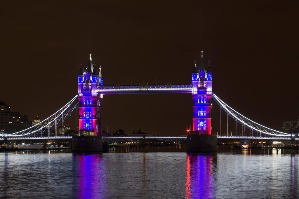Stock Photo: 1801-72824 Tower Bridge Re-lighting, London, United Kingdom. Architect Horace Jones, 2012. View of Tower Bridge capturing new lighting system from HMS Belfast. Red, White, Blue Lighting Scheme.