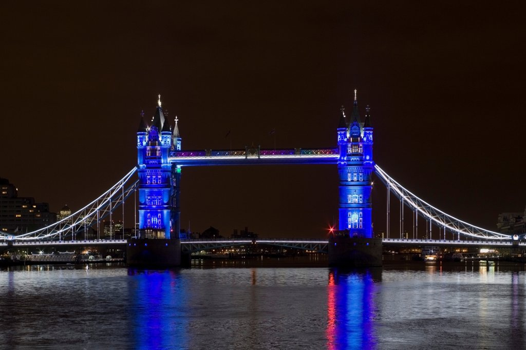 Stock Photo: 1801-72827 Tower Bridge Re-lighting, London, United Kingdom. Architect Horace Jones, 2012. View of Tower Bridge capturing new lighting system from HMS Belfast. Blue Lighting.