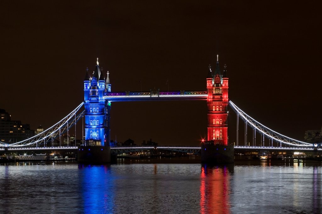 Stock Photo: 1801-72828 Tower Bridge Re-lighting, London, United Kingdom. Architect Horace Jones, 2012. View of Tower Bridge capturing new lighting system from HMS Belfast. Red, White, Blue Lighting.