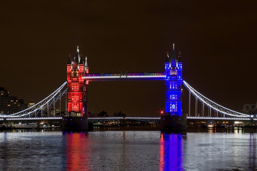 Stock Photo: 1801-72829 Tower Bridge Re-lighting, London, United Kingdom. Architect Horace Jones, 2012. View of Tower Bridge capturing new lighting system from HMS Belfast. Red, White, Blue Lighting.