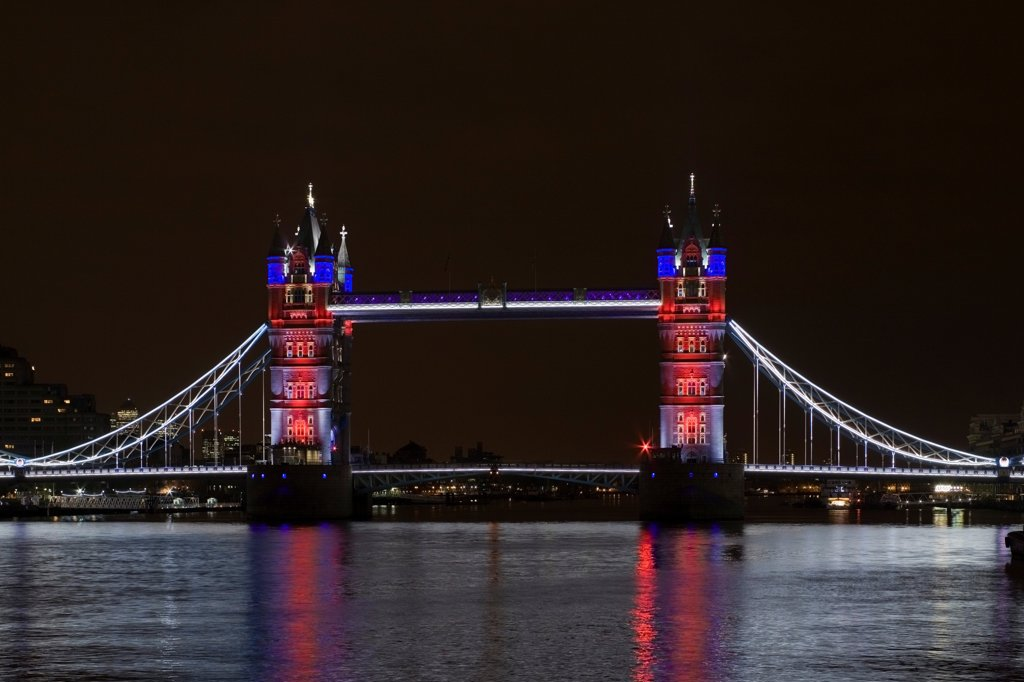 Stock Photo: 1801-72831 Tower Bridge Re-lighting, London, United Kingdom. Architect Horace Jones, 2012. View of Tower Bridge capturing new lighting system from HMS Belfast. Red, White, Blue Lighting.