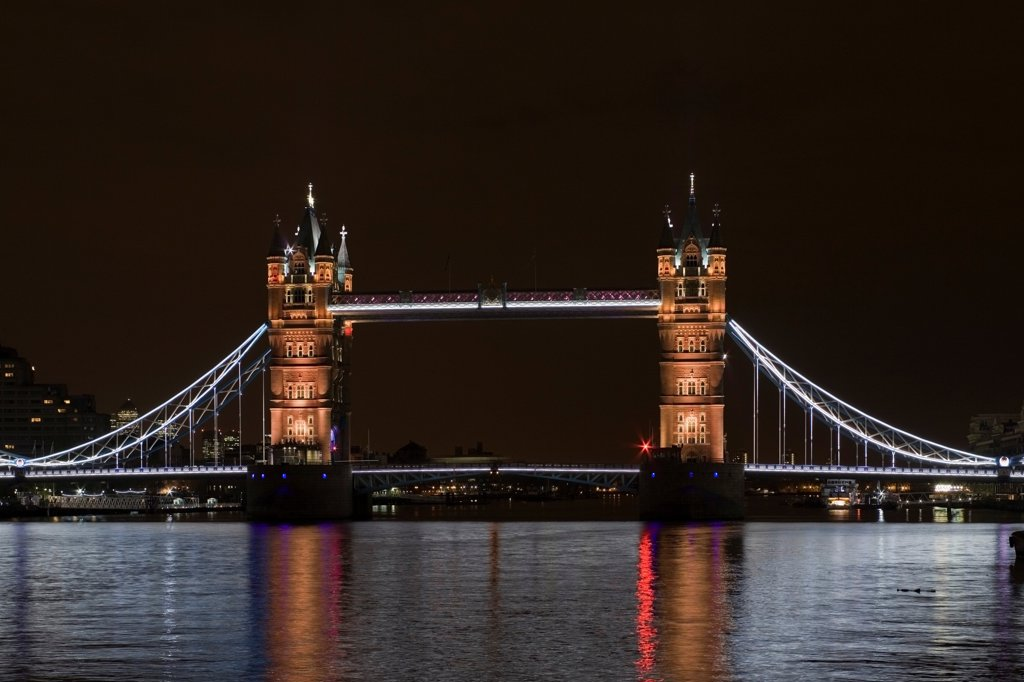 Tower Bridge Re-lighting, London, United Kingdom. Architect Horace Jones, 2012. View of Tower Bridge capturing new lighting system from HMS Belfast. Gold Lighting. : Stock Photo