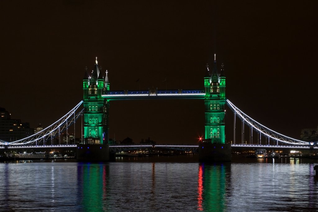 Stock Photo: 1801-72835 Tower Bridge Re-lighting, London, United Kingdom. Architect Horace Jones, 2012. View of Tower Bridge capturing new lighting system from HMS Belfast. Green Lighting.