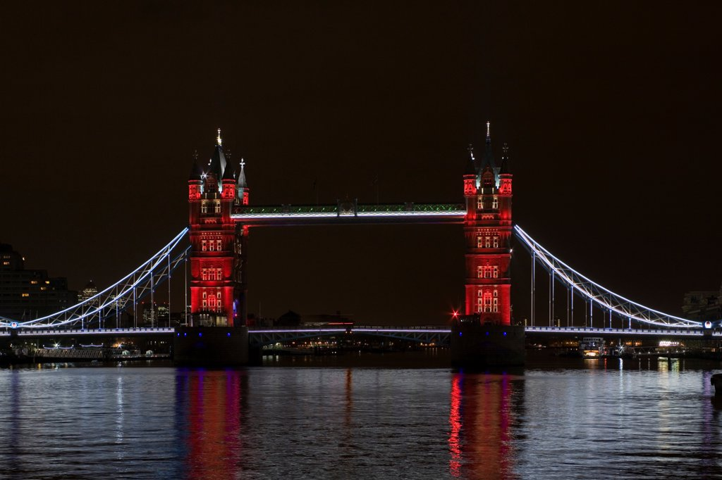 Tower Bridge Re-lighting, London, United Kingdom. Architect Horace Jones, 2012. View of Tower Bridge capturing new lighting system from HMS Belfast. Red Lighting. : Stock Photo