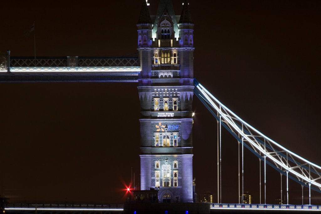 Stock Photo: 1801-72841 Tower Bridge Re-lighting, London, United Kingdom. Architect Horace Jones, 2012. Detail View of Tower Bridge capturing new lighting system from HMS Belfast.