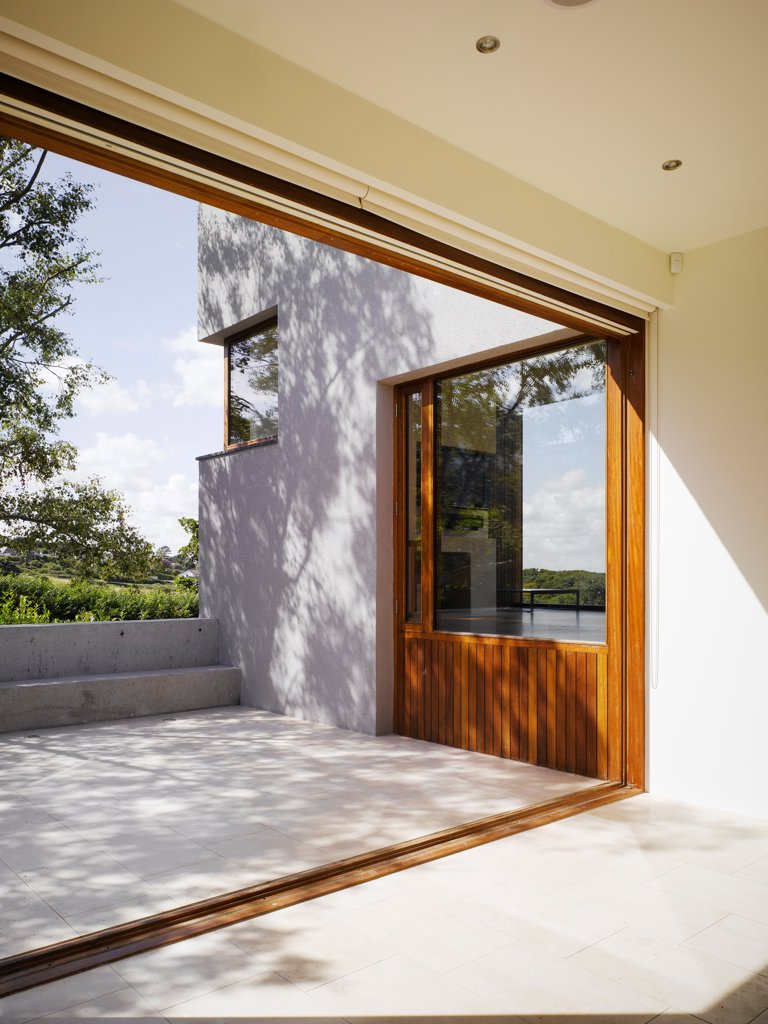 Gray House, Howth, Ireland. Architect O'Donnell & Tuomey, 2008. View of concrete patio from kitchen with folding door opened. : Stock Photo