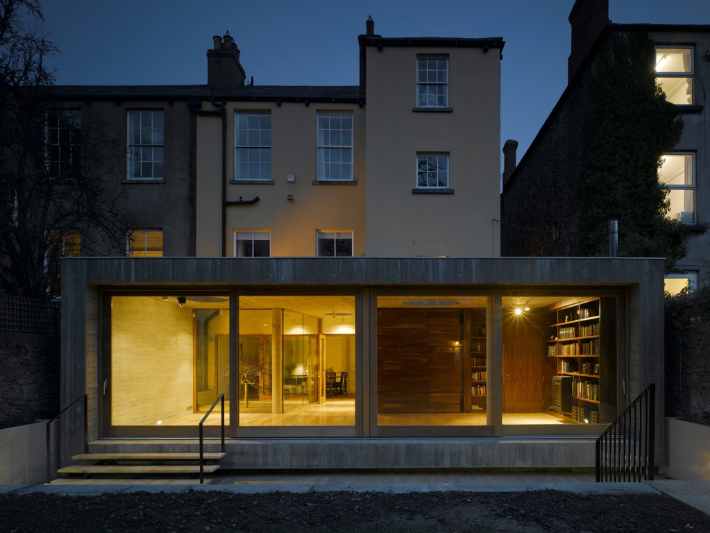 Stock Photo: 1801-73213 Jigsaw House, Dublin, Ireland. Architect McCullough Mulvin, 2012. View of extension from back garden showing existing house, internal lighting, sliding door closed and american walnut internal door open at dusk.