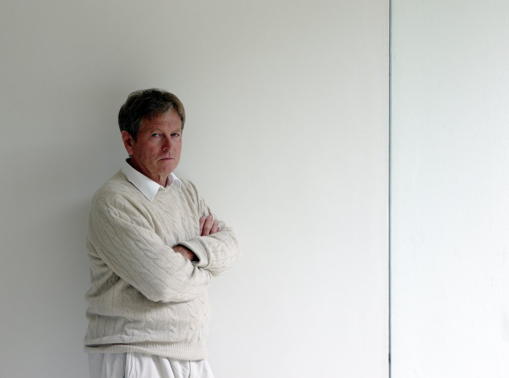 John Pawson at home, London, United Kingdom. Architect: John Pawson, 2010. Portrait of John Pawson standing against a wall in his kitchen/dinning area with arms folded. 3/4 length shot. : Stock Photo